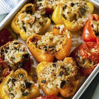 A tray of baked tomatoes and peppers, stuffed with a rice mixture and topped with melted cheese.