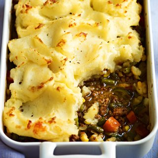 Beef, carrot and gravy pie in a casserole dish, topped with mashed potato
