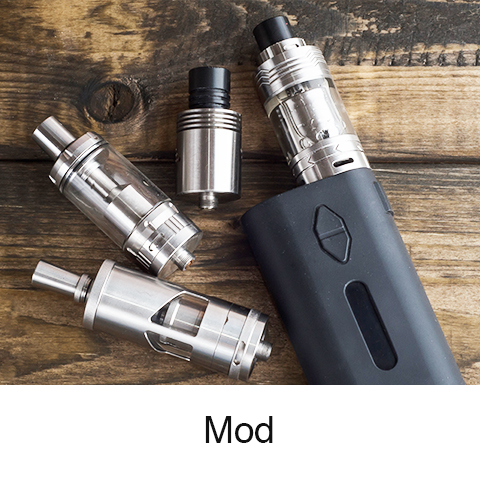 Stoptober - Mod e-cigarette: a thick, black rectangular bottom section with a circular tube attached to the top containing the refillable cartridge and mouthpiece. Two detached refillable cartridges are on the table, as well as a replacement mouthpiece.